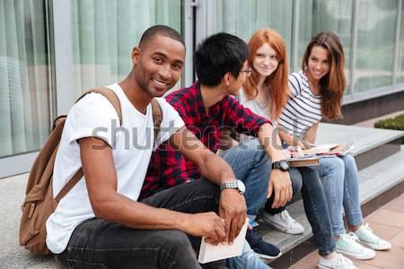 Smiling woman sitting with friends and using mobile phone outdoors Stock photo © deandrobot