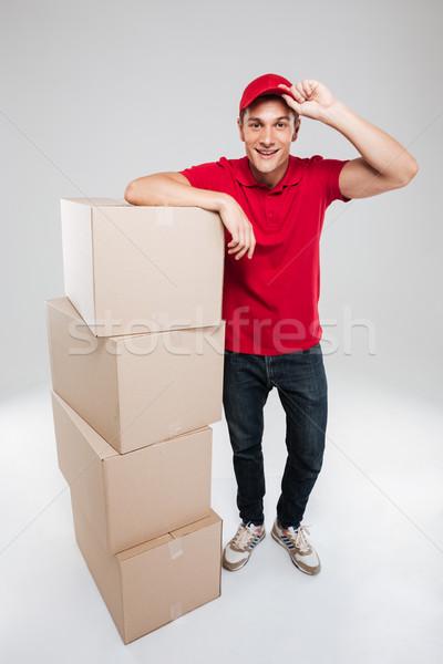 Teljes alakos boldog futár dobozok izolált szürke Stock fotó © deandrobot