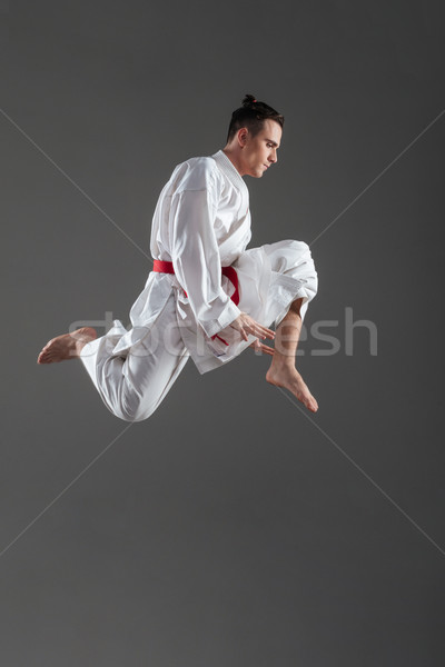 Young attractive sportsman dressed in kimono practice in karate Stock photo © deandrobot