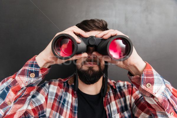 Serious bearded young man standing and looking through binoculars Stock photo © deandrobot