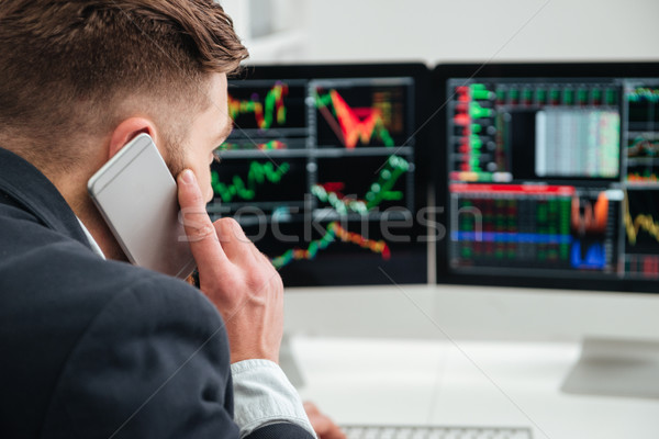 Back view of businessman working and talking on mobile phone Stock photo © deandrobot