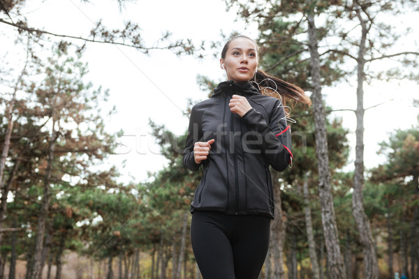 Female runner in warm clothes and earphones running Stock photo © deandrobot