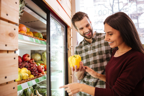 Stock photo: Couple choosing and buying vegetables in grocery shop