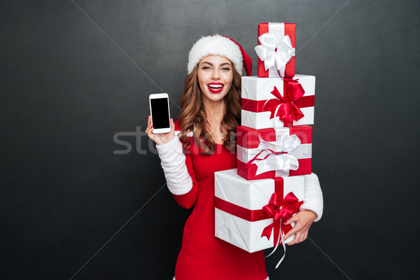 Woman in red christmas outfit showing blank screen mobile phone Stock photo © deandrobot