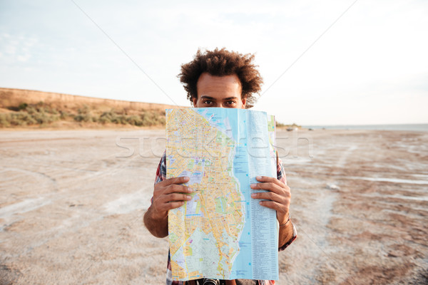 Playful man standing and hiding behind map outdoors Stock photo © deandrobot