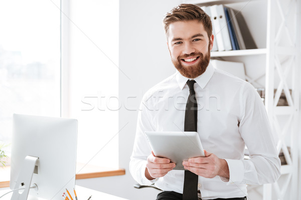 Derűs fiatal üzletember tart táblagép kezek Stock fotó © deandrobot