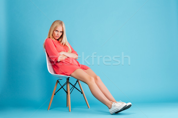 Decepcionado alterar mujer rubia vestido rojo sesión silla Foto stock © deandrobot