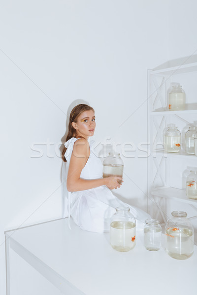 Woman sitting on table and holding gold fish in jar Stock photo © deandrobot
