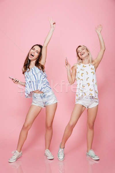 Two laughing teenagers with earphones dancing together Stock photo © deandrobot