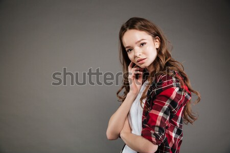 Lovely young woman in plaid shirt standing and posing Stock photo © deandrobot