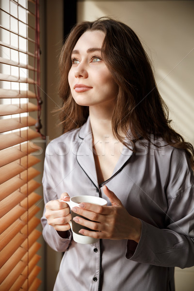 Vertical image of pensive woman with cup of coffee Stock photo © deandrobot