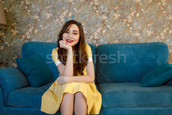 Cheerful young pin-up lady sitting on sofa at home Stock photo © deandrobot