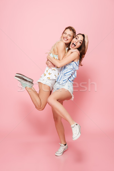 Full length of two cheerful women laighing and having fun Stock photo © deandrobot