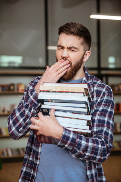 Tired exhausted man holding stack of books and yawning Stock photo © deandrobot