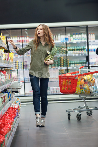Smiling young casual woman with shopping cart looking at products Stock photo © deandrobot