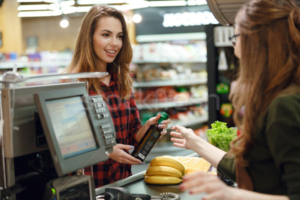 Smiling young lady standing in supermarket shop Stock photo © deandrobot