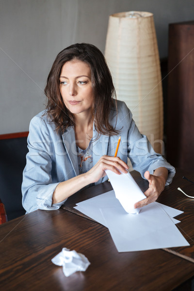 Thinking concentrated woman writer sitting indoors Stock photo © deandrobot