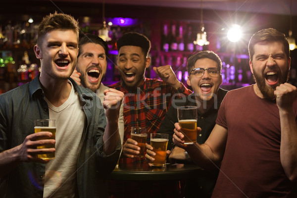 Four happy men holding beer mugs and gesturing Stock photo © deandrobot