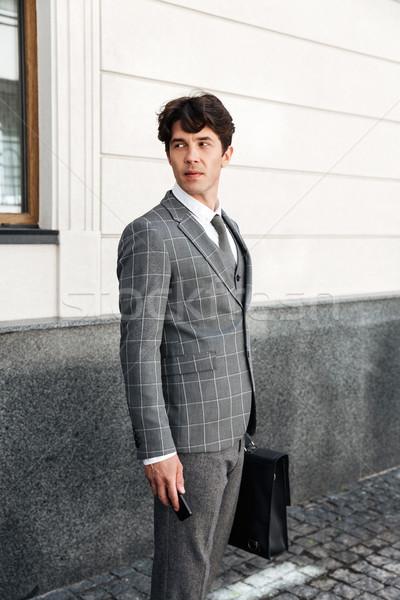 Confident handsome businessman in suit holding car keys Stock photo © deandrobot