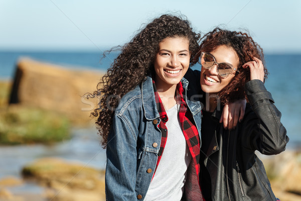 Smiling african woman friends walking outdoors at beach. Stock photo © deandrobot