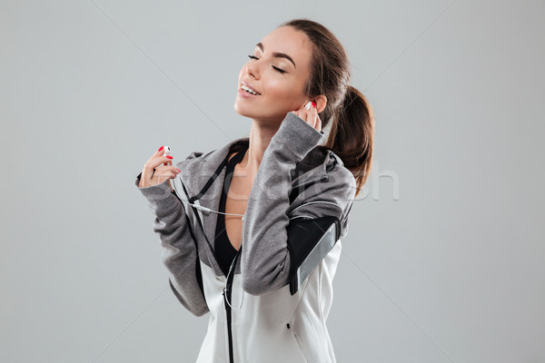Pleased sports woman listening music with closed eyes Stock photo © deandrobot