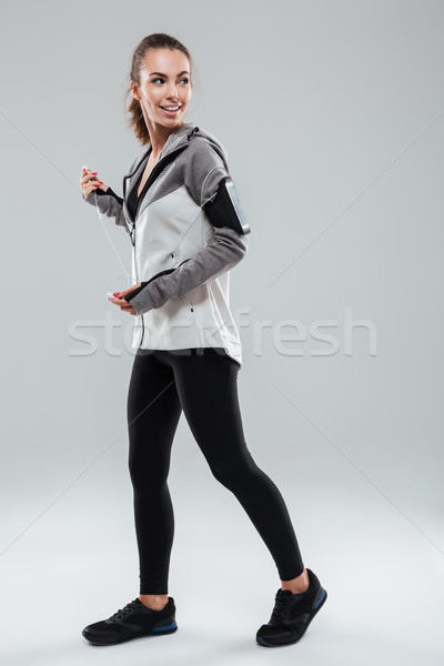 Full length image of happy female runner in warm clothes Stock photo © deandrobot