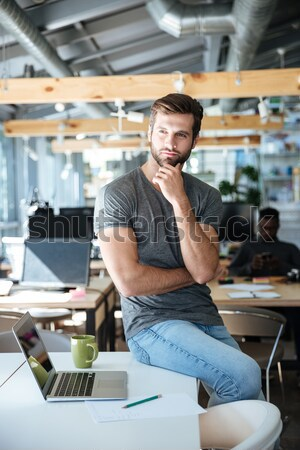 Happy young man sitting on table in office chatting Stock photo © deandrobot