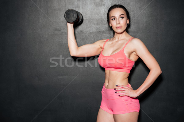 Concentrated sports young lady holding dumbbell. Stock photo © deandrobot
