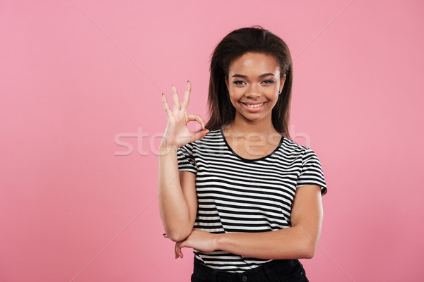 Portrait of a casual afro american woman showing ok gesture Stock photo © deandrobot