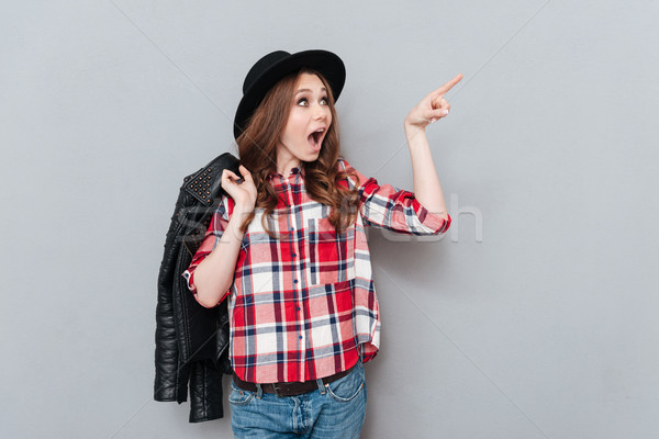 Woman in hat and plaid shirt pointing finger away Stock photo © deandrobot