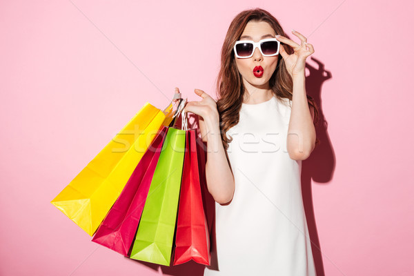 Shocked young brunette woman with shopping bags Stock photo © deandrobot