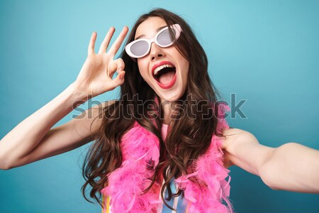 Happy young brunette woman showing peace gesture Stock photo © deandrobot