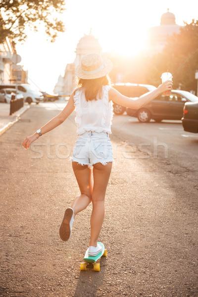 Hátulnézet kép fiatal nő kint sétál gördeszka Stock fotó © deandrobot