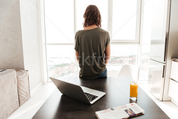 Back view of casual woman standing near table Stock photo © deandrobot