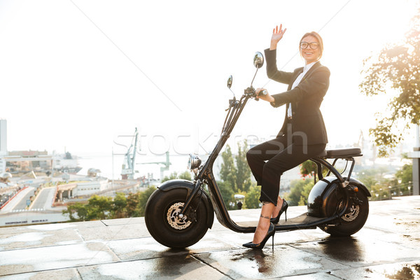 Full length Side view image of smiling business woman Stock photo © deandrobot