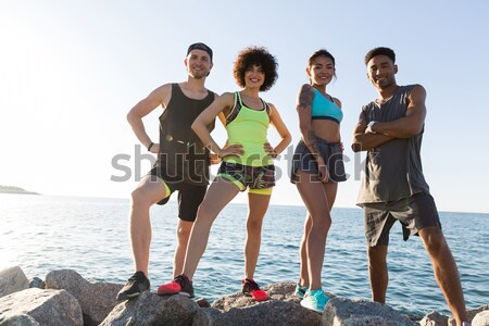 Group of happy fitness people posing on stones after training Stock photo © deandrobot