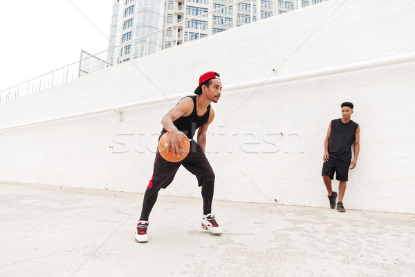 Concentrated young african sports men play basketball Stock photo © deandrobot