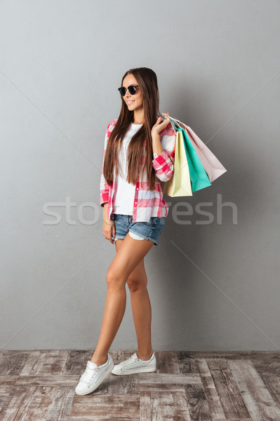 Full length portrait of a smiling woman in casual wear, holding  Stock photo © deandrobot