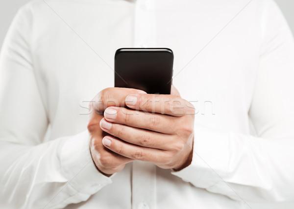 Imagen joven teléfono blanco camisa Foto stock © deandrobot