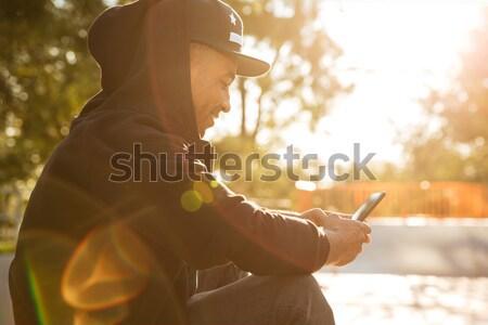 изображение улыбаясь скейтбордист глядя мобильного телефона экране Сток-фото © deandrobot