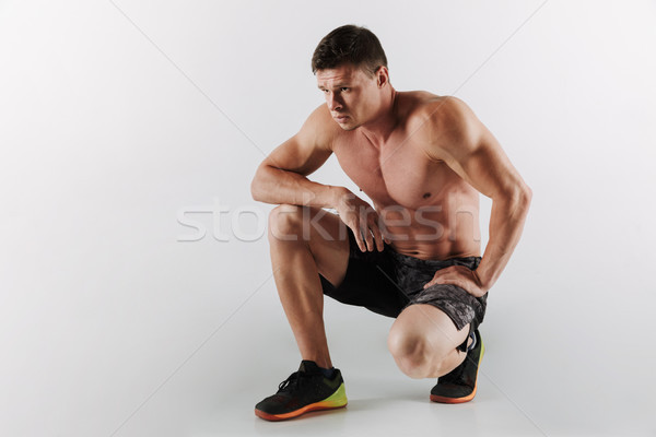 Serious young sportsman make sport exercises Stock photo © deandrobot