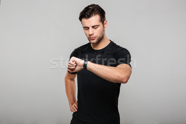 Portrait of a young sportsman looking at his wristwatch Stock photo © deandrobot