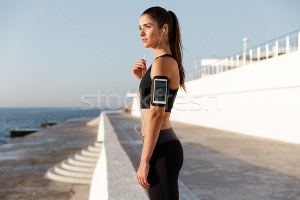 Stock photo: Serious young sports woman listening music