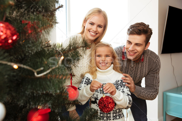 Happy father, mother and little daughter decorating Christmas tr Stock photo © deandrobot