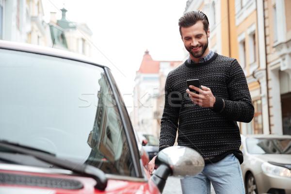 肖像 満足した 若い男 セーター 携帯電話 立って ストックフォト © deandrobot