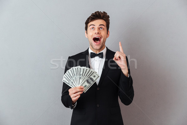 Screaming man in official suit holding money pointing. Stock photo © deandrobot