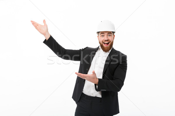 Cheerful bearded business man in protective helmet pointing away Stock photo © deandrobot