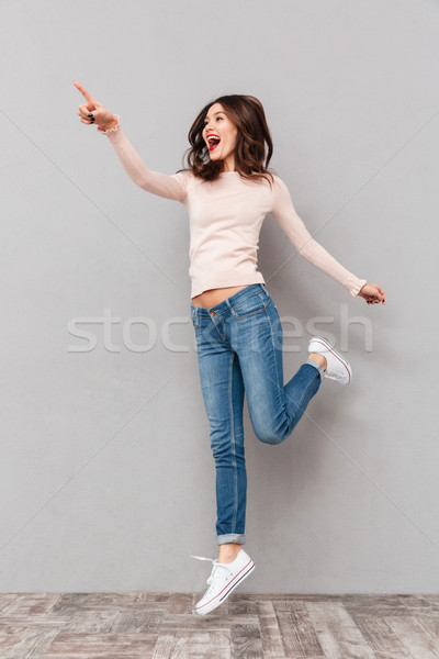 Full-length photo of cheerful woman looking aside gesturing with Stock photo © deandrobot
