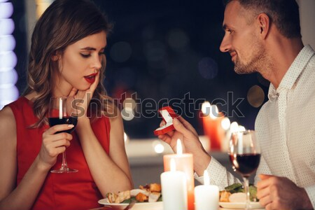 Young woman eating and flirting with her man while have romantic dinner Stock photo © deandrobot