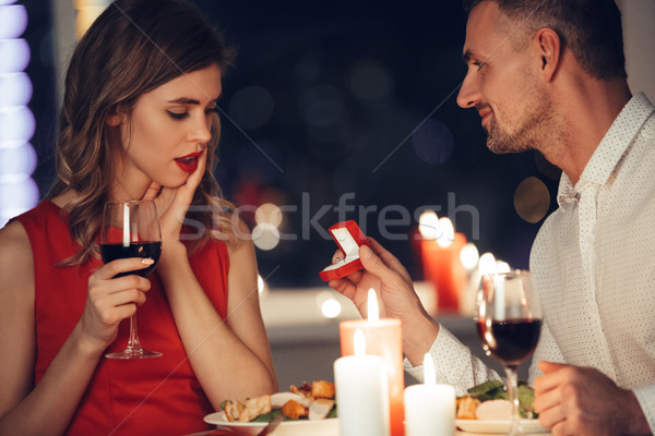 Shocked woman looking at her man giving her box with engagement ring Stock photo © deandrobot
